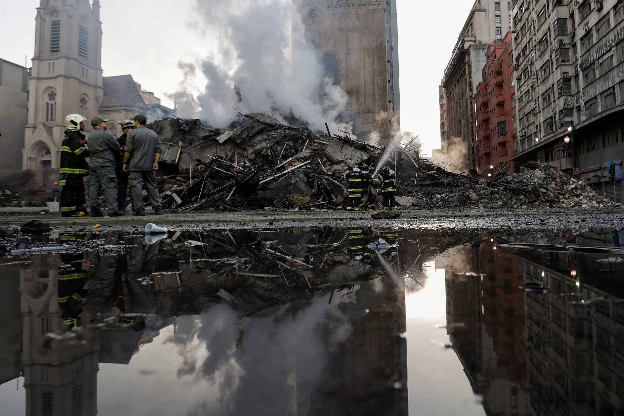 Brazilian firefighters stand in front of the debris of a 24-storey building that collapsed after a fire broken out the previous day resulting in at least one person dead, in downtown Sao Paulo, Brazil, May 2, 2018. (EPA Photo)