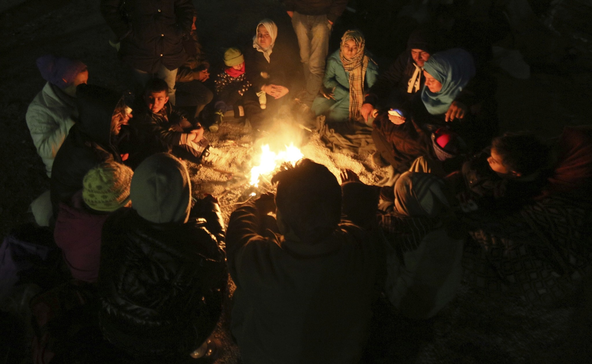 Miigrants sit around a campfire after crossing the border between Slovenian and Austria in Spielfeld, Austria. (AP Photo)