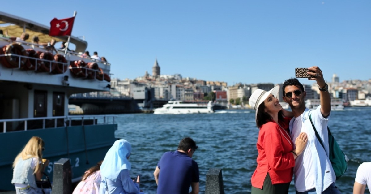 A couple takes a picture in front of the Galata Tower overlooking the Golden Horn in Istanbul, July 2, 2019. (AA Photo)