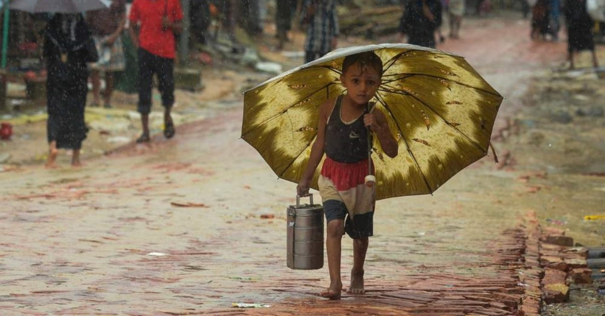 A Rohingya refugee boy shelters under an umbrella during a monsoon rainfall at the Kutupalong refugee camp, Ukhia, Sept. 12, 2019.