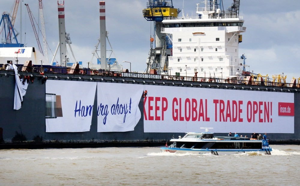 Workers hang a banner reading u2018Hamburg Ahoy! Keep Global Trade Open!, for the lobbyist organisation Initiative Neue Marktwirtschaft (INSM) on the side of a floating dock at the Blohm and Voss shipyards in preparation for the upcoming G20 Summit.