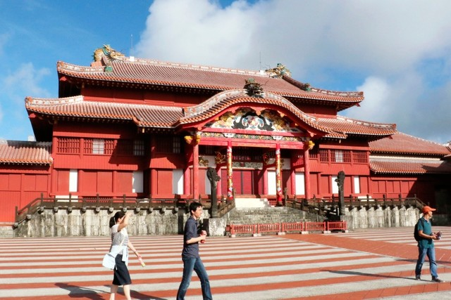 In this October 2016, photo, people walk in front of the main temple of Shuri Castle. (Kyodo News via AP)