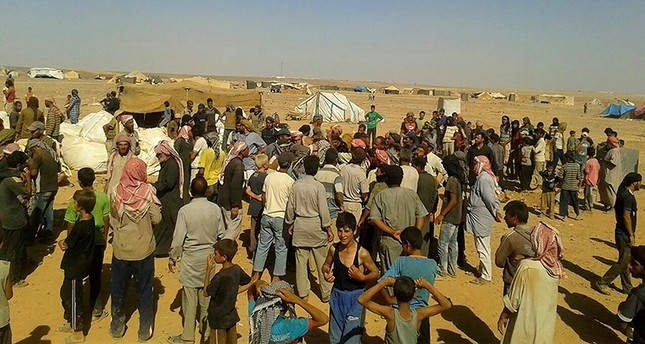 People gather to take basic food stuffs and other aid from community leaders charged with distributing equitably the supplies to the 64,000-person refugee camp called Ruqban on the Jordan-Syria border. (AP Photo)