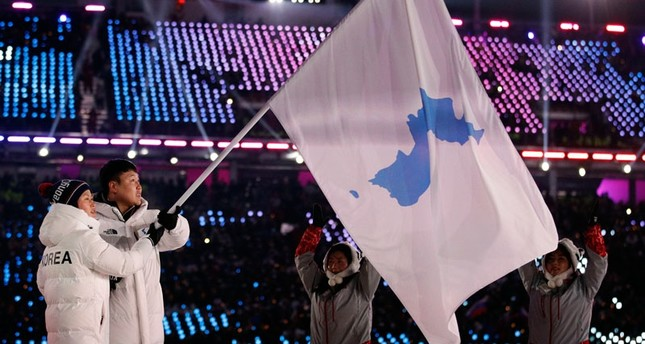North Korea's Hwang Chung Gum and South Korea's Won Yun-jong carries the flag during the opening ceremony of the 2018 Winter Olympics in Pyeongchang, South Korea, Friday, Feb. 9, 2018. (AP Photo)
