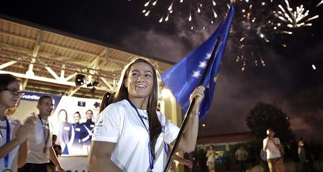Kosovo Judoka competitor Malinda Kelmendi waves Kosovo flag during a flag handover ceremony in Kosovo capital Pristina on Friday July 29, 2016. (AP Photo)