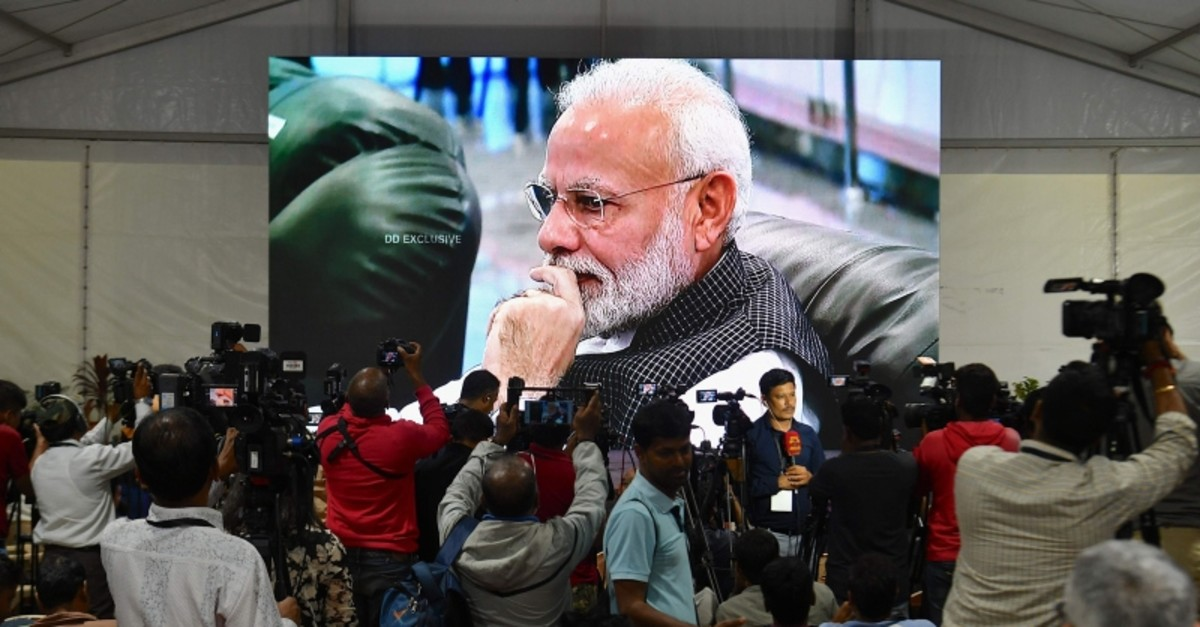 Media cover the development as PM Modi is seen on a tv screen as he watches the live broadcast of the soft landing of spacecraft Vikram Lander of Chandrayaan-2 on the surface of the moon at ISTRAC center in Bangalore early on September 7, 2019. (AFP)