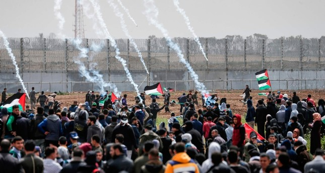 Tear gas canisters fall among Palestinian protesters during a demonstration near the border with Israel in Malaka east of Gaza City on March 30, 2019. (AFP Photo)