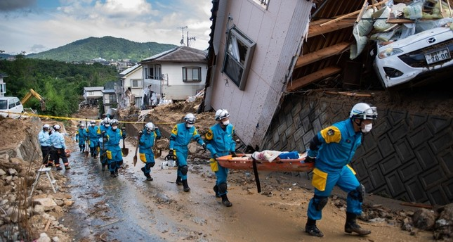 Police arrive to clear debris scattered on a street in a flood hit area in Kumano, Hiroshima prefecture, Japan, July 9, 2018. (AFP Photo)