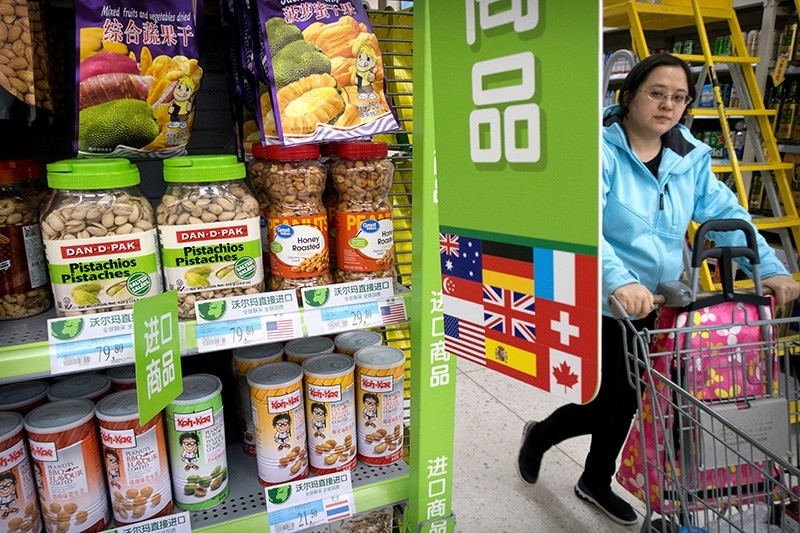 A woman pushes a shopping cart past a display of nuts imported from the United States at a supermarket in Beijing (AP Photo)