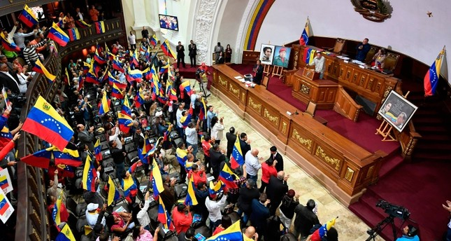 Members of the Venezuelan National Constituent Assembly (ANC) wave flags as its president Diosdado Cabello speaks, during a session at the ANC headquarters on August 12, 2019, in Caracas. (AFP Photo)