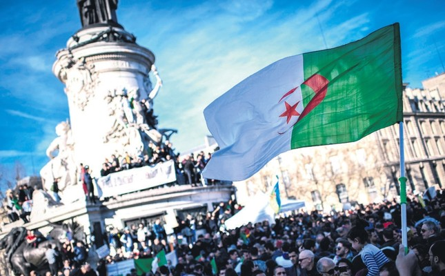 A protester holds up the Algerian flag during a rally against the Algerian president's bid for a fifth term in office, at the Place de la Republique in Paris, February 24, 2019.