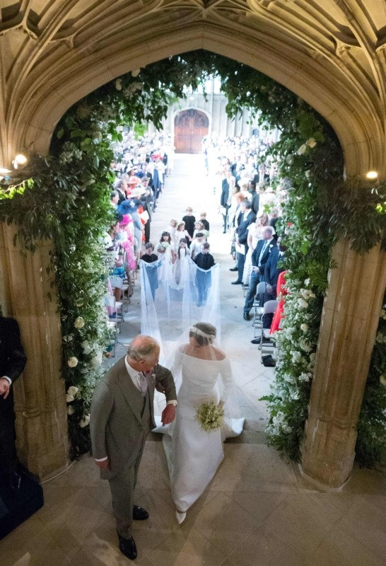 Meghan Markle (R), accompanied by Britain's Prince Charles, Prince of Wales (L) walks down the aisle in St George's Chapel, Windsor Castle, in Windsor, on May 19, 2018 during their wedding ceremony.