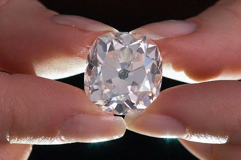 A member of Sotheby's staff poses holding a 26.27 carat, cushion-shaped, white diamond, for sale at Sotheby's auction house in London on May 22, 2017 (AFP Photo)