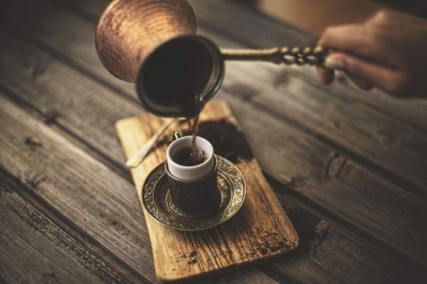 A coffee maker pours Turkish coffee into a traditional cup from a copper coffee pot. (iStock Photo)