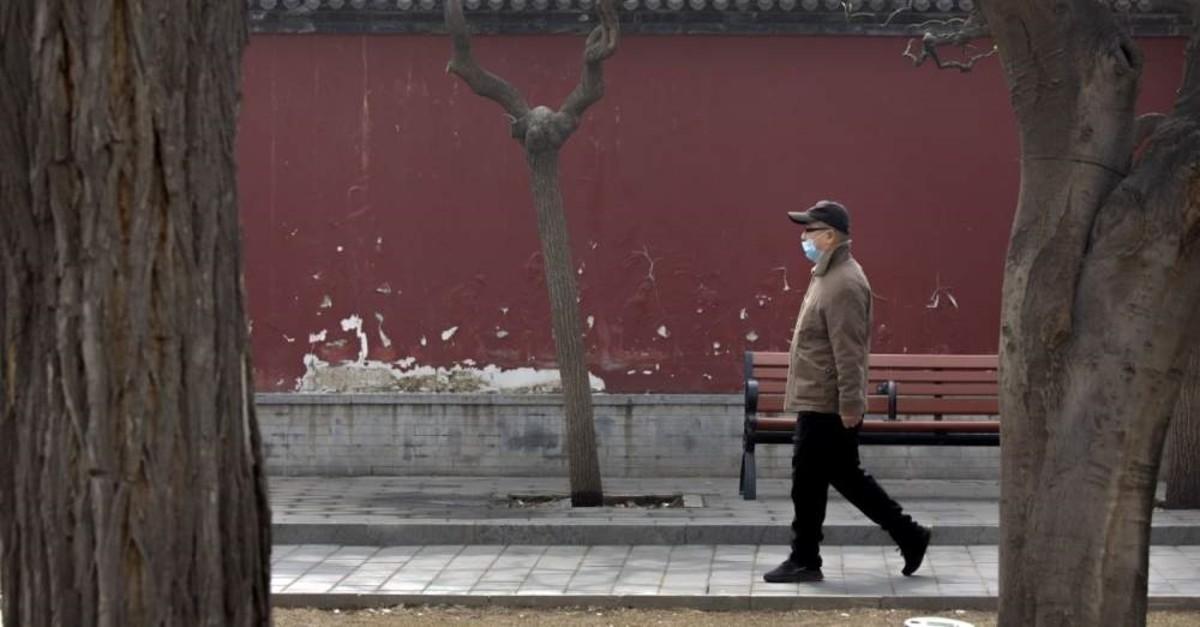 A man wearing a face mask walks through a public park in Beijing, Friday, Feb. 21, 2020. (AP Photo)