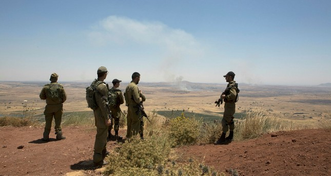 Israeli soldiers observe smoke rising from Syrian village as a result of fighting near the city of Quneitra, in the Golan Heights, as seen from the Israeli side of the border, 26 June 2017. (EPA Photo)