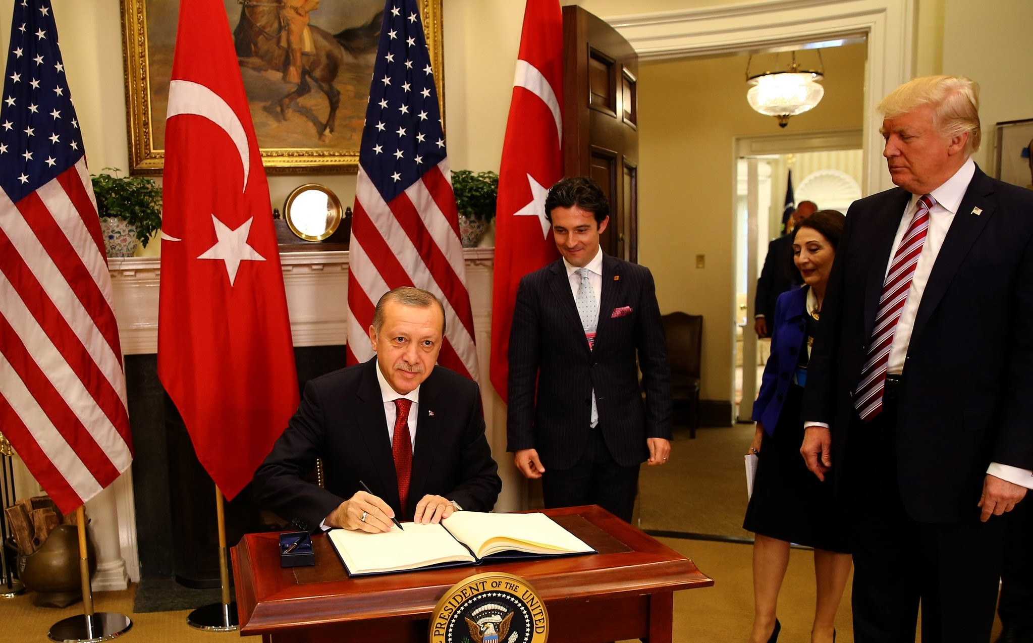 President Recep Tayyip Erdou011fan (L) signs a book of honor during his visit to the U.S. as President Donald Trump, first on the right, watches the ceremony, Washington, May 16, 2017.
