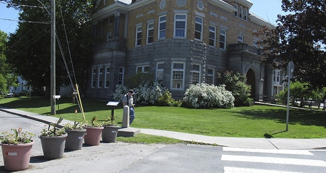 In this photo taken on June 8, 2017 in Derby Line, Vt., a border post and planters show the U.S.-Canadian border where it leads to the Haskell Opera House and library, a building located in the two countries. (AP Photo)