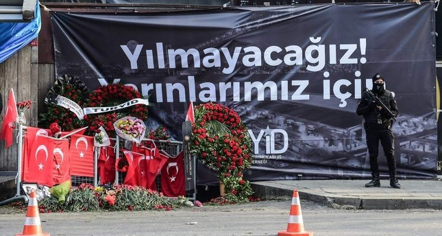 A police officer stands guard in front of a banner that reads in Turkish For our tomorrow, we will not fall down, in front of Reina nightclub, Istanbul, Jan. 3, 2017. AFP Photo