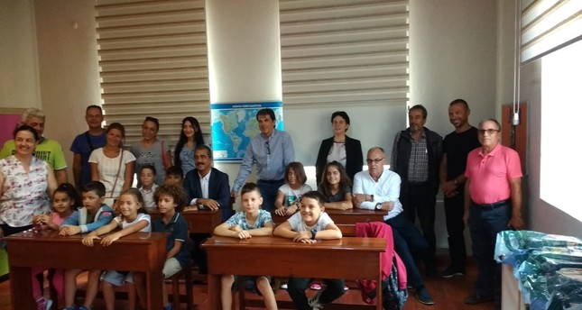 Students pose with their parents and administrators of schools in Gökçeada.