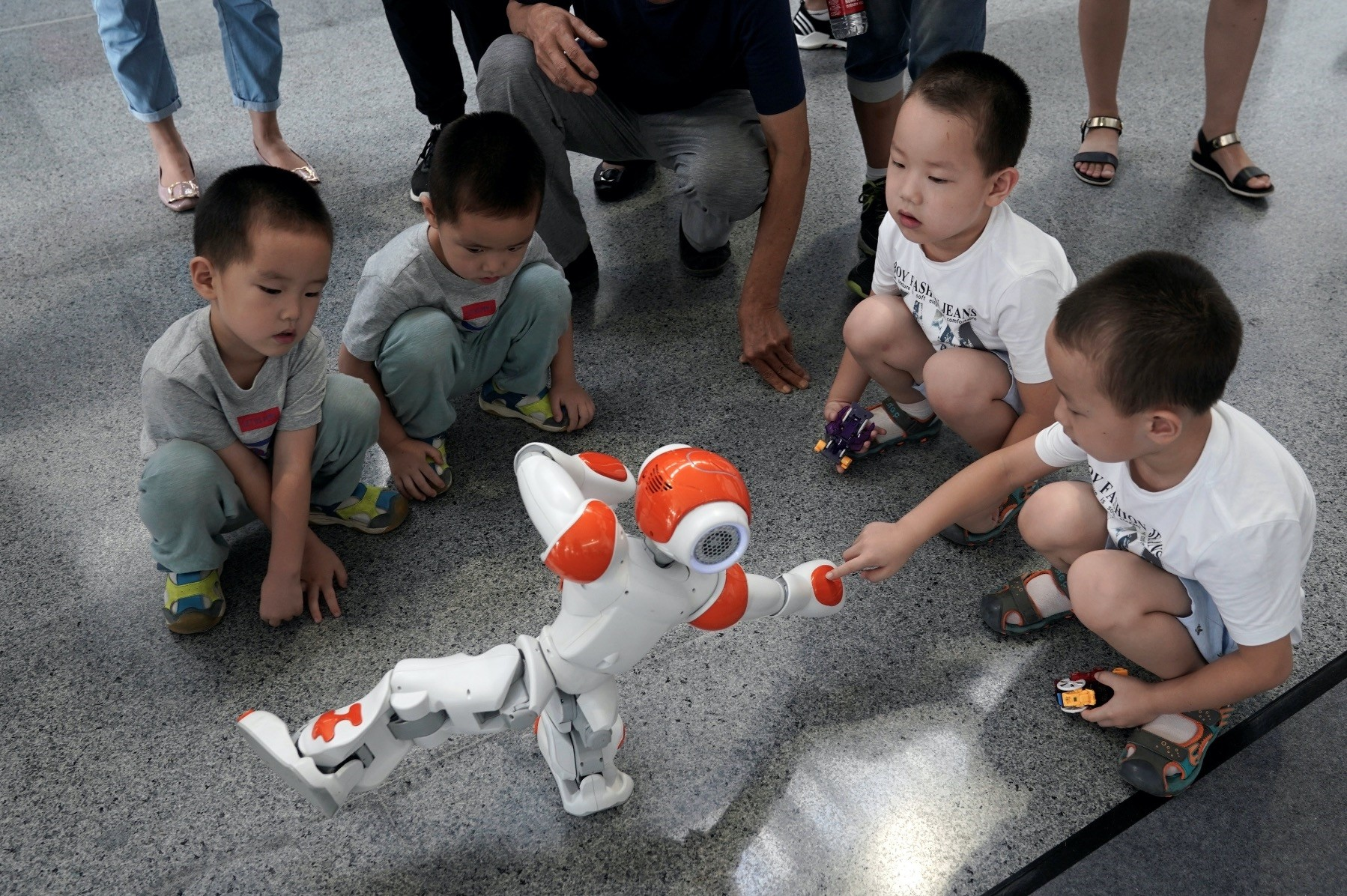 A boy touches a robot as it performs Taiji, a traditional form of Chinese martial arts, at the World Robot Conference in Beijing.