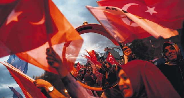 People celebrate President Erdoğan's and the AK Party's victory in the presidential and parliamentary elections, outside the AK Party headquarters, Istanbul, Sunday.