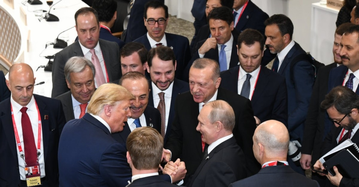 President Recep Tayyip Erdou011fan (C), U.S. President Donald Trump (L) and Russian President Vladimir Putin (R) have a quick talk during the G20 summit of world leaders in Osaka, Japan, June 30, 2019.
