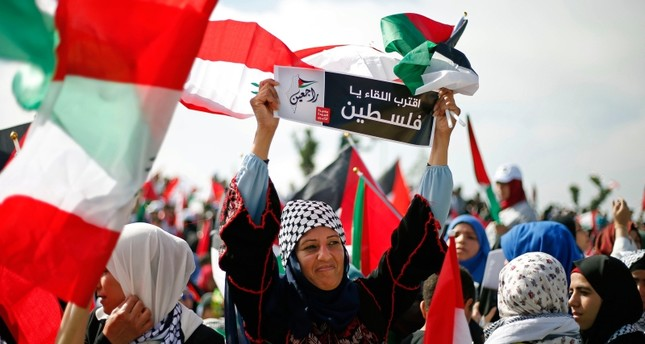 A Palestinian woman living in Lebanon holds a placard with Arabic that reads, We will meet soon Palestine, we will return, during a rally to mark the 70th anniversary of what Palestinians call their nakba (AP File Photo)