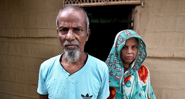 Abdul Suban, a farmer, and his wife pose for a photograph outside their home in Nellie village, in Morigaon district, in the northeastern state of Assam, India July 25, 2018. (Reuters Photo)
