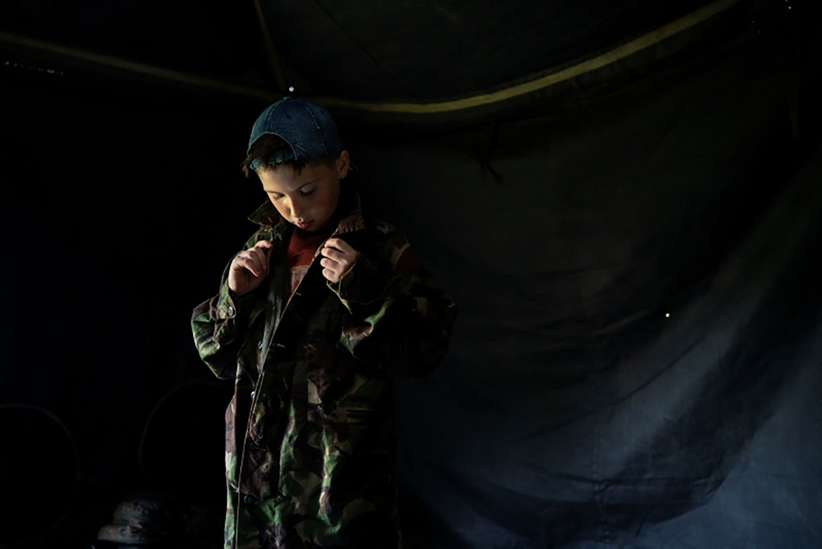 A young participant of the camp buttons up a camouflage shirt as he prepares for an exercise.