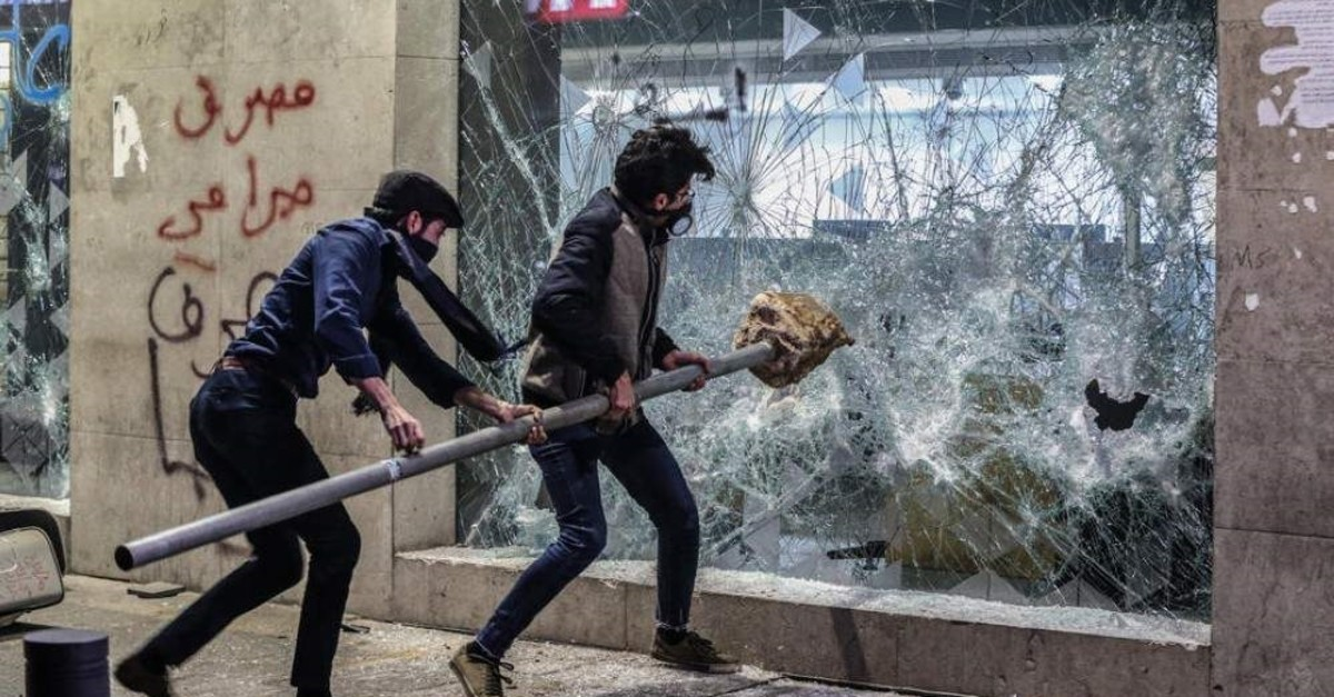 Anti-government protesters clash with riot police as they block a road and calling for 'the fall of the rule of the bank' during a protest in front of the Lebanese Central Bank headquarters, Beirut, Jan. 14, 2020. (EPA Photo)