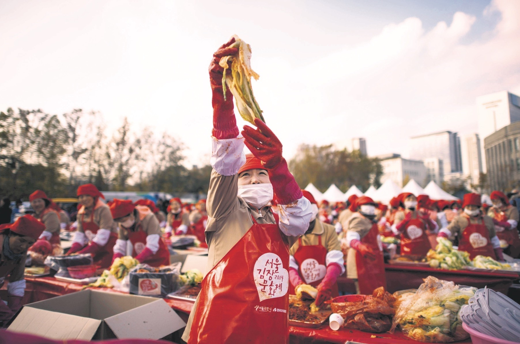A participant holds a handful of kimchi in the air as she joins some 2,000 others in a kimchi-making event outside the city hall in Seoul.