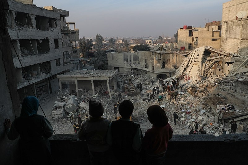 Children look out from their destroyed home as White Helmets volunteers search for survivors after several air strikes destroyed civil buildings in Hamoria city, al-Ghouta. (EPA Photo)