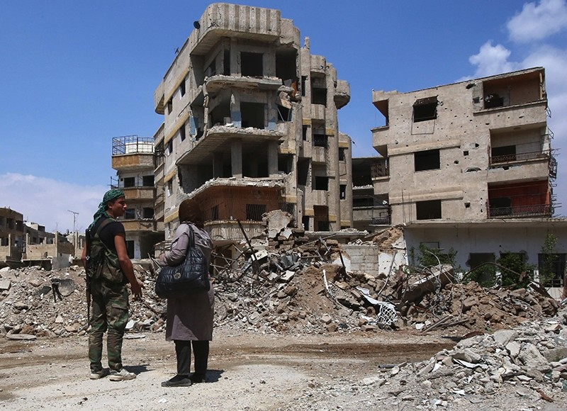 An Assad regime forces soldier talks with a woman in a destroyed street in the former opposition-held town of Zamalka in eastern Ghouta, on the outskirts of the capital Damascus, Syria, April 11, 2018. (AFP Photo)