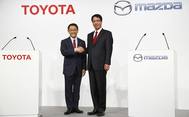In this May 13, 2015 file photo, Toyota Motor Corp. President Akio Toyoda, left, and Mazda Motor Corp. President Masamichi Kogai pose for photographers prior to a press conference in Tokyo. (AP Photo)