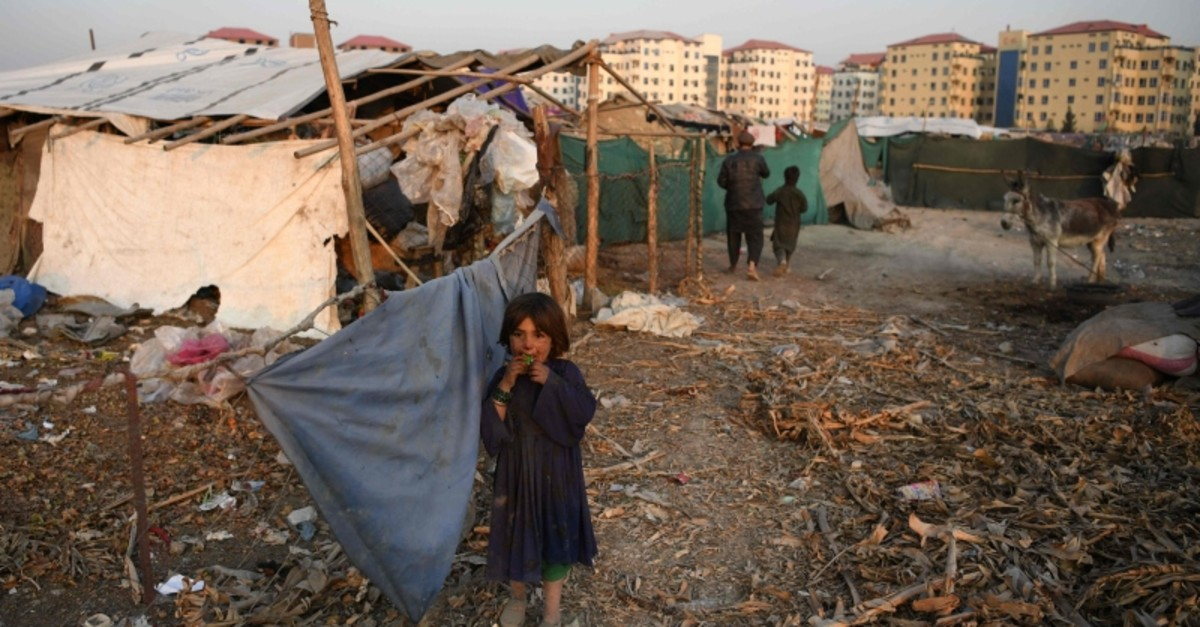 An internally displaced Afghan girl stands outside a temporary home at a refugee camp in Kabul, Dec. 24, 2019 (AFP Photo)