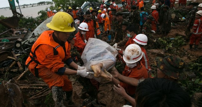 Rescue workers carry the body of a landslide victim in Paung township, Mon state on Aug. 10, 2019. AFP Photo