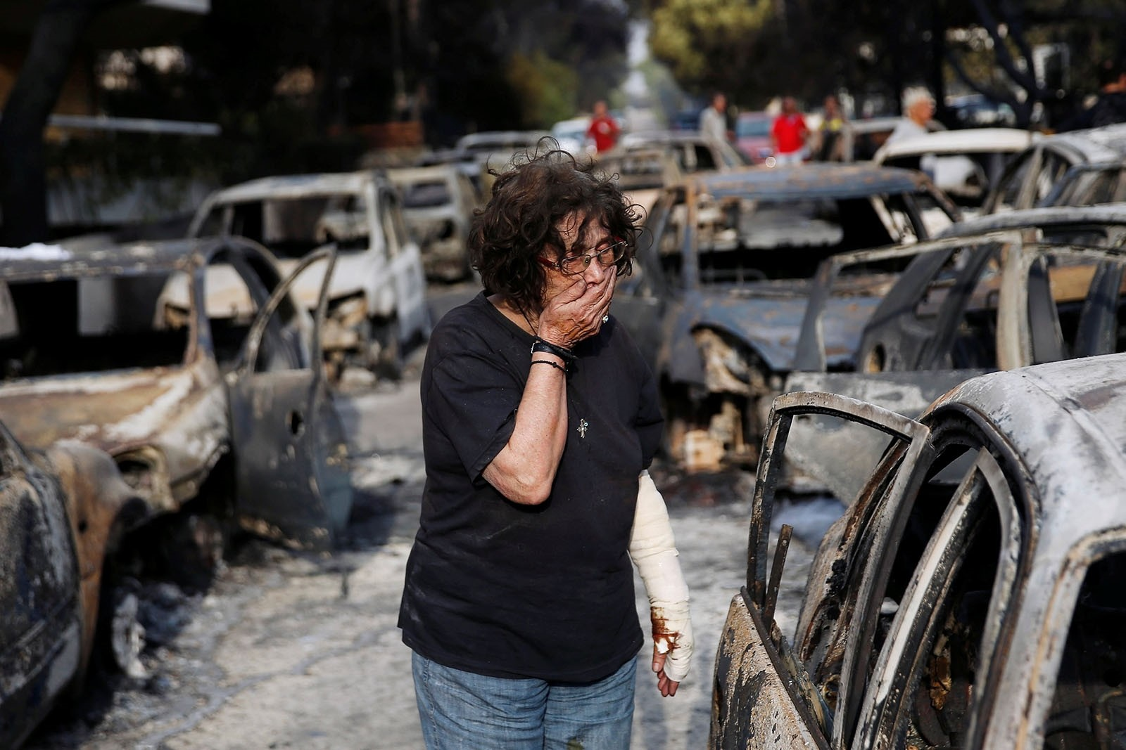 A woman reacts as she tries to find her dog, following a wildfire at the village of Mati, near Athens, Greece July 24, 2018.