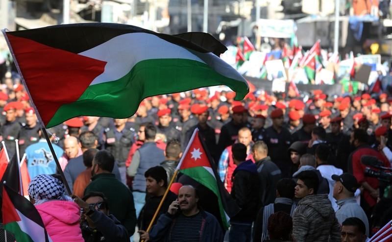 A Jordanian protester waves a Palestinian flag as another carries a Jordanian national flag during a demonstration against the US president's decision to recognise Jerusalem as the capital of Israel ( AFP Photo)