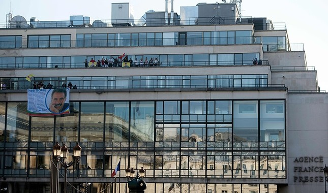 Terrorist PKK supporters wave flags and banners picturing jailed terrorist leader Abdullah Öcalan as they take part in a demonstration on the balconies, after invading the headquarters of AFP in Paris, on October 15, 2017 (AFP Photo)