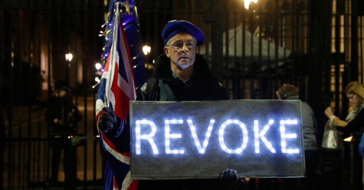 An anti Brexit campaigner stands outside the entrance to Downing Street with flags and a banner in London, Wednesday, March 20, 2019. (AP Photo)