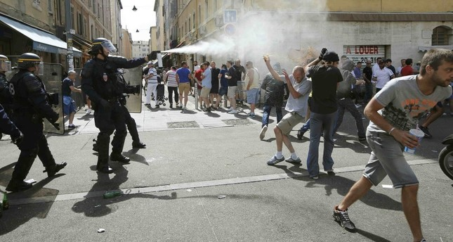 Police use tear gas on supporters near port of Marseille before the game.