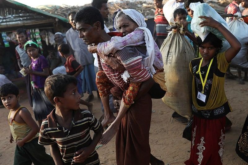 Rohingya refugee Suray Khatun, 70, is carried by her son Said-A-Lam, 38, as they enter Kutupalong refugee camp, near Cox's Bazar, Bangladesh a day after crossing the Myanmar border, Nov. 20, 2017 (Reuters Photo)