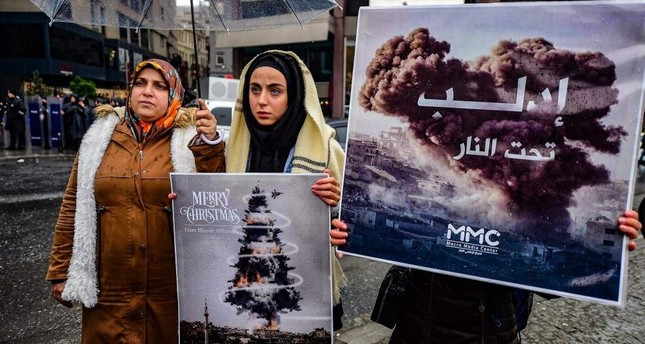 Protestors hold placards reading bomb Christmas tree during a protest against the Syrian military operation in Idlib, northwestern Syria, taking place near the Russian Consulate, in Istanbul, on Dec. 28, 2019 Photo by Yasin AKGUL / AFP
