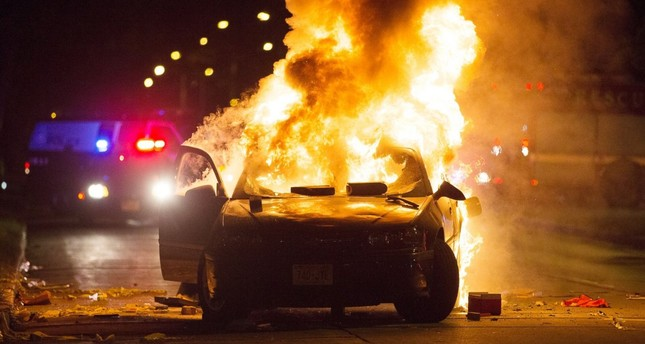 A car burns as a crowd of more than 100 people gathers following the fatal shooting of a man in Milwaukee, Saturday, Aug. 13, 2016.emAP Photo/em