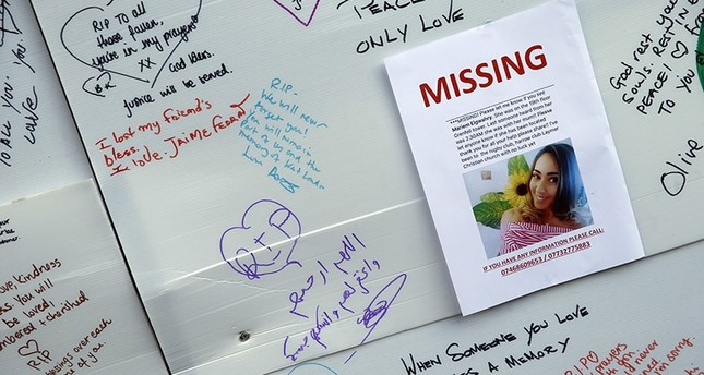 A schoolgirl looks at messages of support for victims, missing and those affected by the massive fire in Grenfell Tower, in London, Thursday, June 15, 2017. (AP Photo)