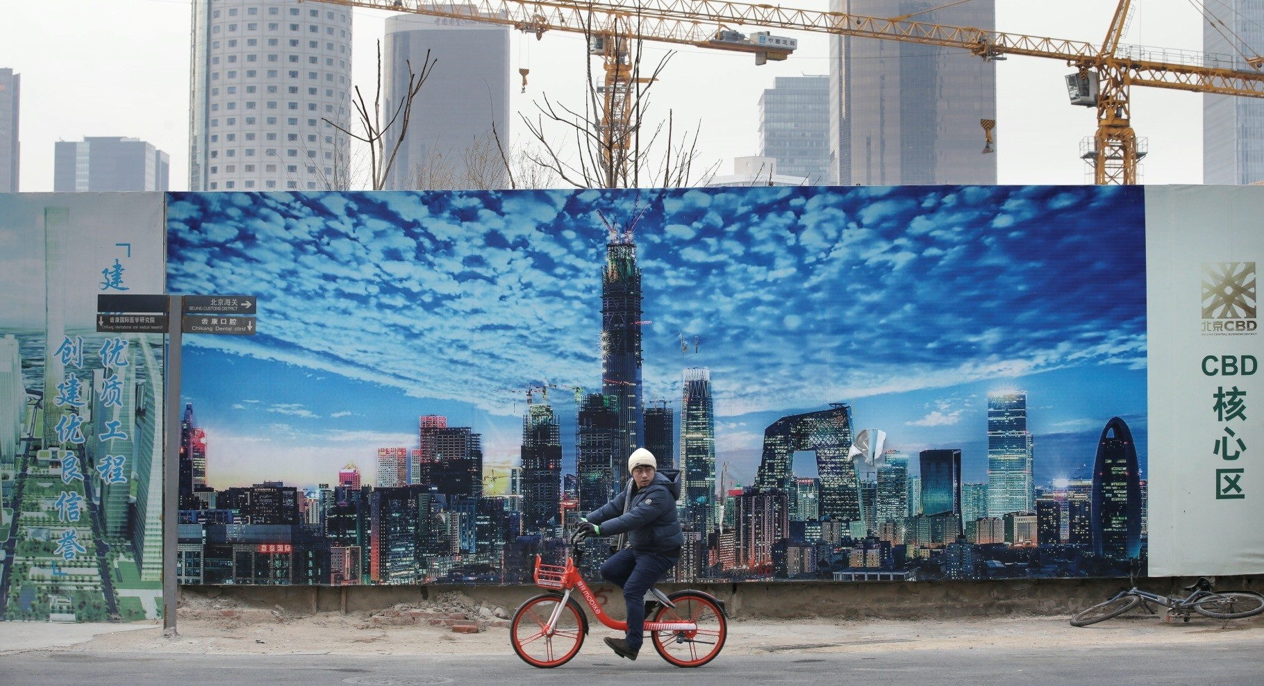 A man cycles in front a construction site in Beijing's central business area, China, Jan. 18, 2019.