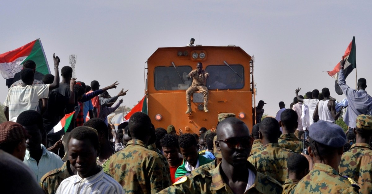 Sudanese military and demonstrators attending a sit-in block a train from passing through, during a protest outside the Defence Ministry in Khartoum, Sudan, April 14, 2019.