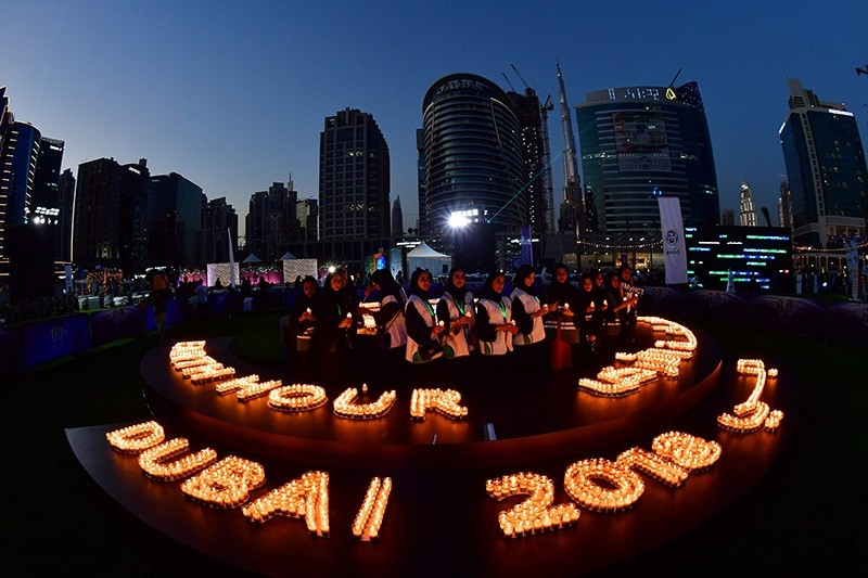 People light candles after the building lights were switched off for the Earth Hour environmental campaign in Dubai on March 24, 2018 (AFP Photo)