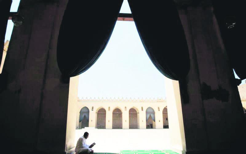 An Egyptian man reads the Quran inside awl-Hakim bi-Amr Allah Mosque in Cairo, Egypt.